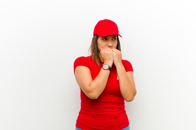 Mulher entrega olhando preocupado, ansioso, estressado e com medo, roer unhas e olhando para o espaço lateral da cópia