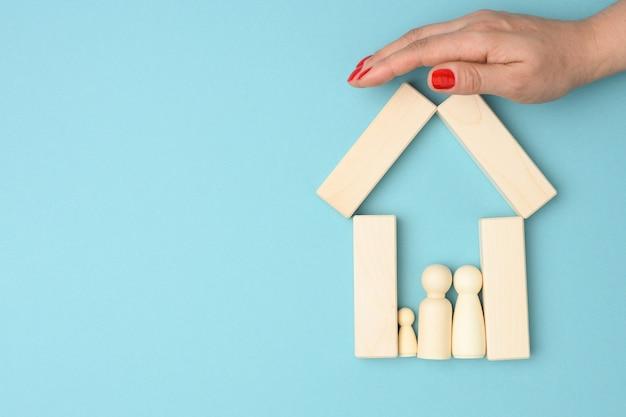 Mulher entrega uma casa de madeira em miniatura com a família