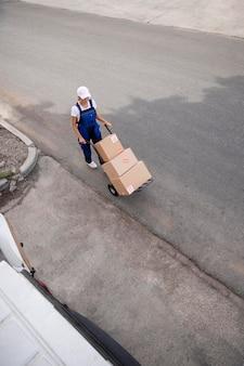 Mulher entregadora de longa distância carregando caixas