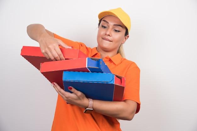 Mulher entregadora de pizza consertando caixas de pizza em fundo branco.