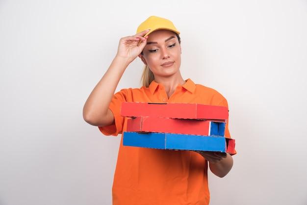 Mulher entregadora de pizza segurando caixas de pizza em fundo branco.