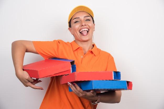 Mulher entregadora de pizza segurando caixas de pizza enquanto estica a língua no fundo branco.