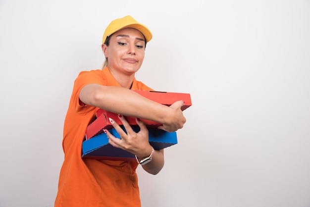 Mulher entregadora de pizza segurando cuidadosamente as caixas de pizza no fundo branco.