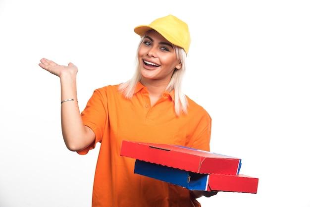 Mulher entregadora de pizza segurando pizzas, mostrando a mão no fundo branco. foto de alta qualidade