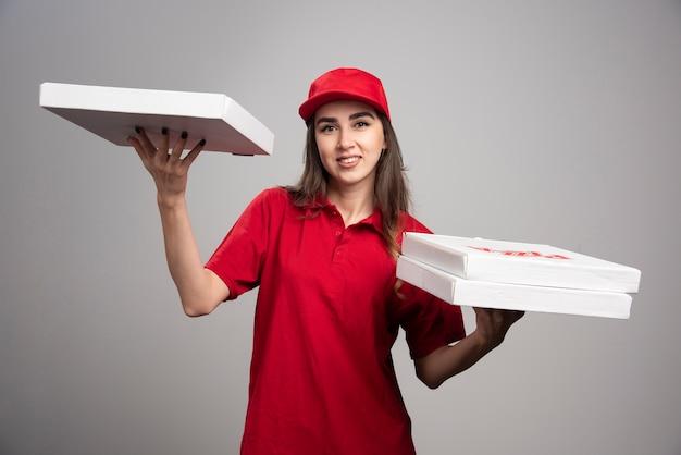Mulher entregadora posando com pedidos de pizza.