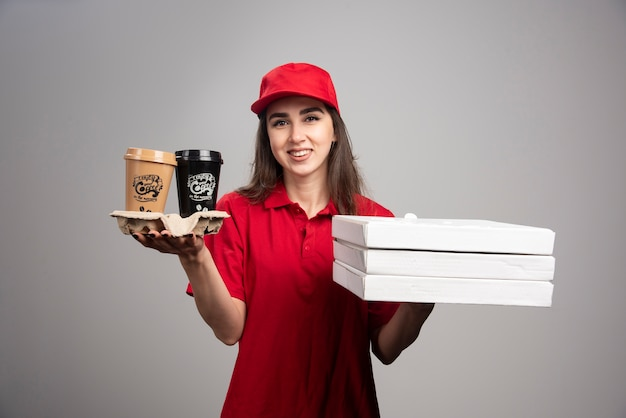 Mulher entregadora segurando pizza e xícaras de café na parede cinza.