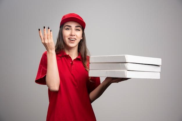 Mulher entregadora segurando pizzas na parede cinza.