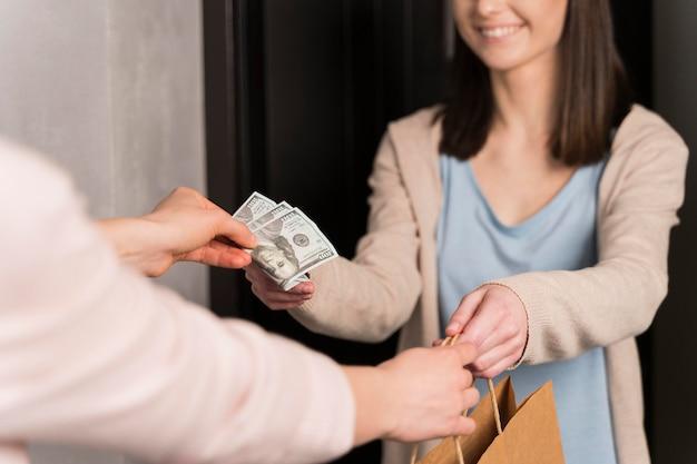 Mulher entregando saco de papel e receber notas