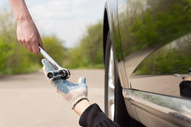 Mulher entregando uma chave de boca ou chave inglesa para um mecânico que trabalhava embaixo de seu carro
