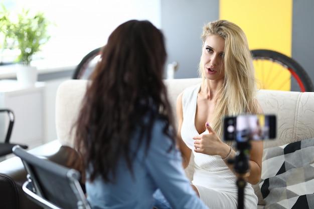 Mulher entrevista a loira e grava em seu smartphone.