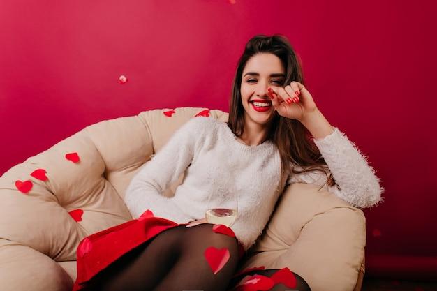 Mulher entusiasmada de cabelos escuros e unhas vermelhas sorrindo para a câmera