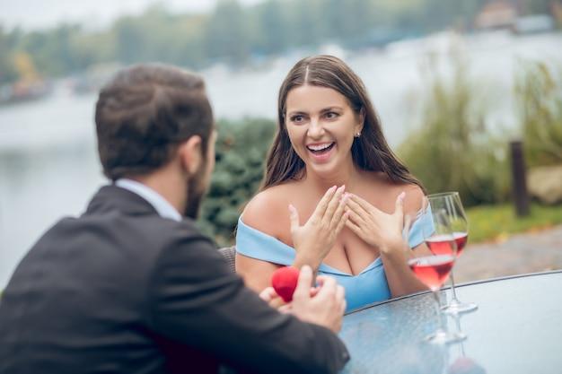 Mulher entusiasmada e surpresa emocional com a boca aberta e o homem com a caixa vermelha de costas para a câmera sentado em um café ao ar livre