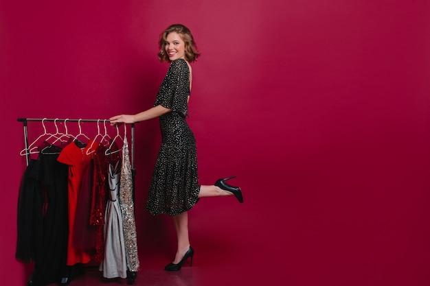 Mulher entusiasmada em um vestido longo, posando em uma perna só no vestiário