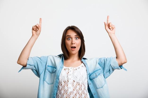 Mulher entusiasmada surpresa apontando para cima