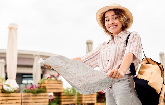 Mulher entusiasta viajando sozinha com um mapa