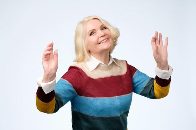 Mulher envelhecida alegre na dança de suéter colorido.