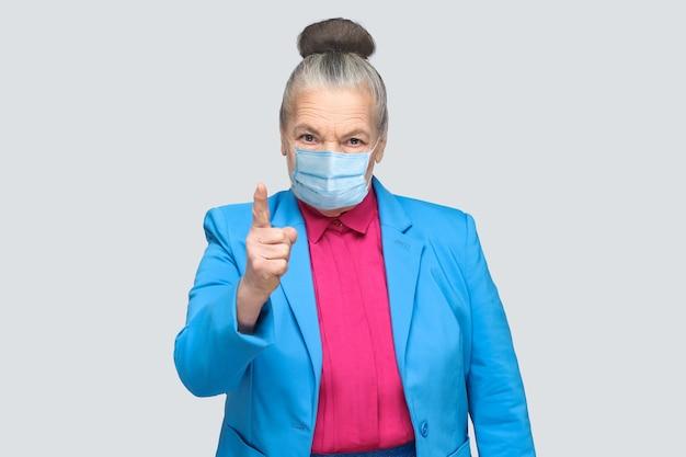 Mulher envelhecida com raiva com máscara médica cirúrgica avisando você. avó com terno azul claro e camisa rosa em pé com cabelo grisalho colecionado. foto de estúdio interno, isolada em fundo cinza