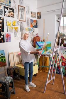 Mulher envelhecida elegante. mulher idosa elegante usando jeans e tênis, amando pintar, olhando para a foto