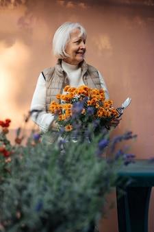 Mulher envelhecida feliz trabalhando com flores desabrochando no jardim.