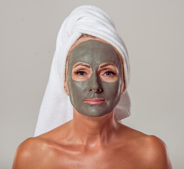 Mulher envelhecida média bonita com uma máscara da argila em sua cara.