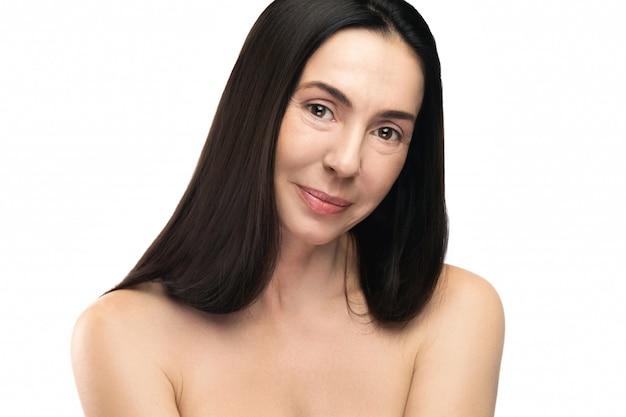 Mulher envelhecida média bonita no fundo branco