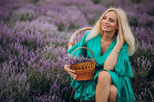 Mulher envelhecida média em um campo de lavanda