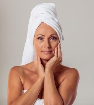Mulher envelhecida média na toalha tocando seu rosto