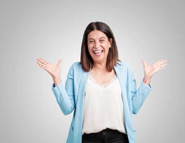 Mulher envelhecida média que grita feliz, surpreendida por uma oferta ou por uma promoção, escancarado, saltando e orgulhoso