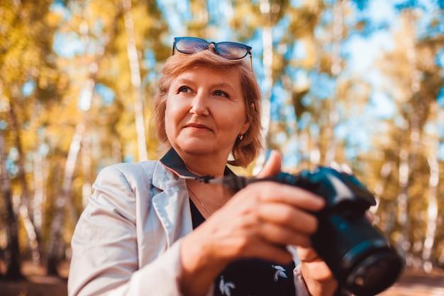 Mulher envelhecida média, verificando as imagens na câmera na floresta de outono