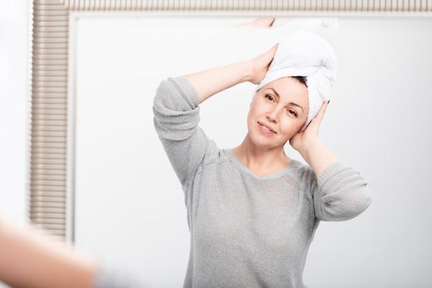 Mulher envelhecida sorridente, aplicar creme anti-envelhecimento