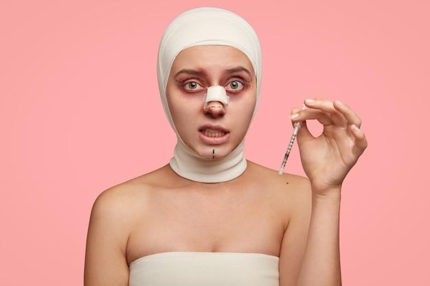 Mulher envergonhada com linhas marcadas no rosto, carrega seringa