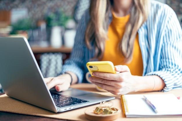 Mulher enviando mensagens de texto no celular e no laptop