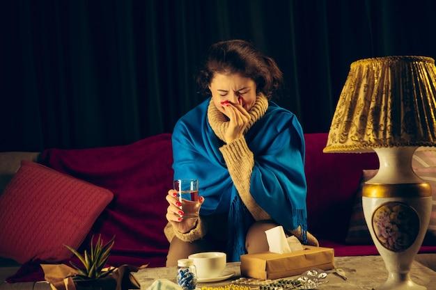 Mulher envolta em uma manta parece doente, espirrando e tossindo, sentada em casa dentro de casa