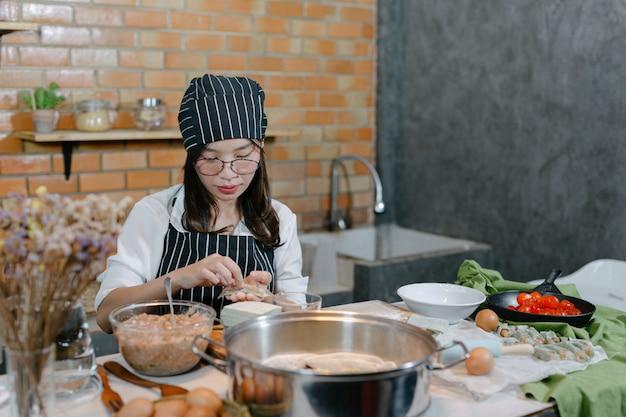 Mulher envolvida em bolinhos asiáticos cozinhar comida.