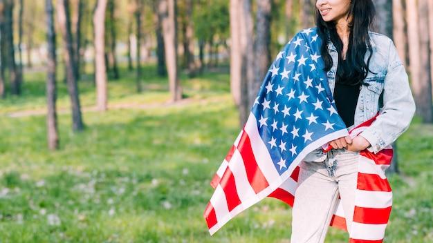 Mulher envolvida na bandeira americana no parque