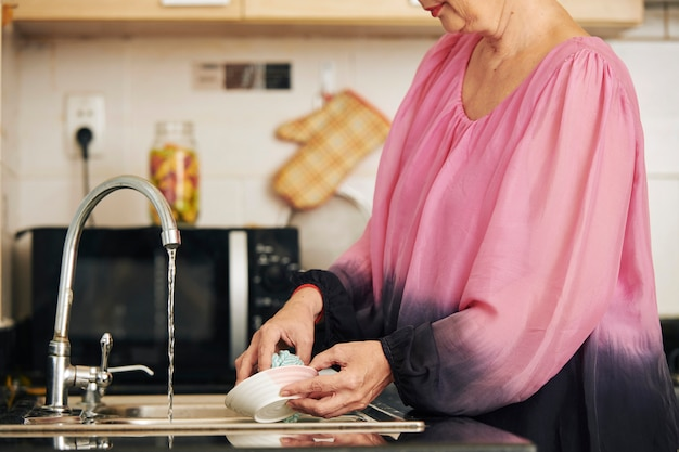 Mulher enxaguando o prato com água da torneira