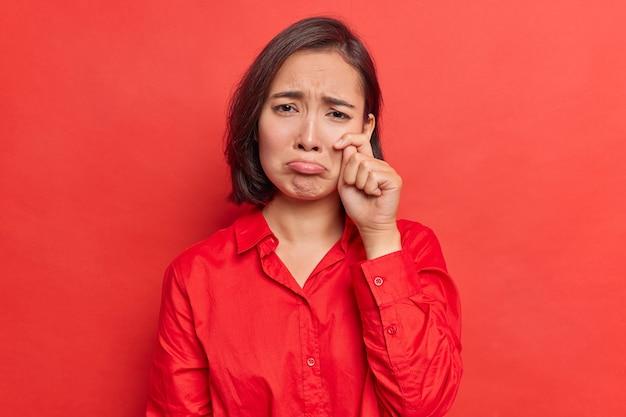 Mulher enxuga as lágrimas depois de assistir a um filme comovente triste, tem o coração partido, sente descontentamento usa uma camisa posa em vermelho brilhante