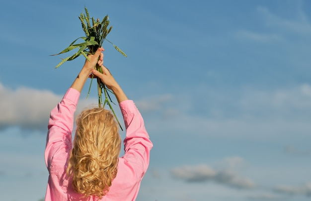 Mulher ergueu as mãos para o céu nas mãos de espigas de trigo. céu azul com nuvens, foco seletivo com espaço de cópia, ideia para banner ou plano de fundo