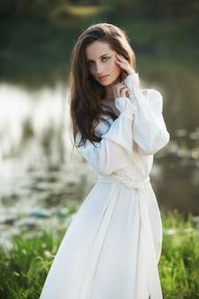 Mulher esbelta linda em um vestido branco longo caminha de manhã perto do lago. menina de cabelos castanho com cabelos longos caminha na grama da vila, cosméticos naturais e maquiagem