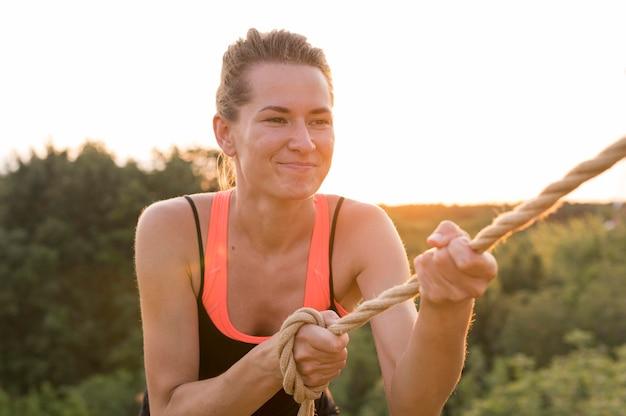 Mulher escalando com a ajuda de um amigo e uma corda