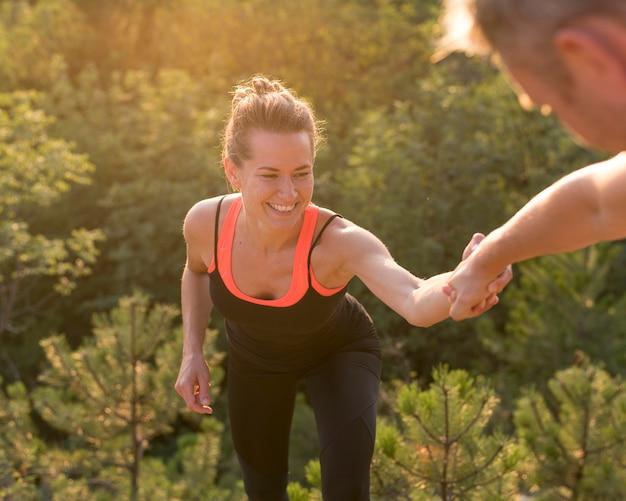 Mulher escalando com a ajuda de um amigo