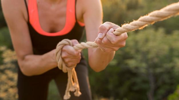 Mulher escalando com a ajuda de uma corda
