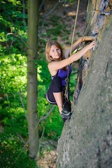 Mulher, escalando, ligado, um, parede rocha, com, corda, e, carabinas, acoplado