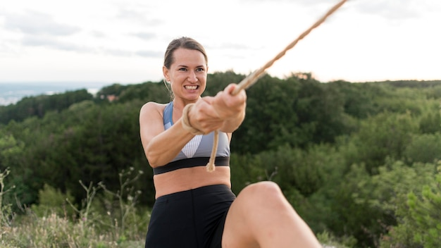 Mulher escalando segurando uma corda