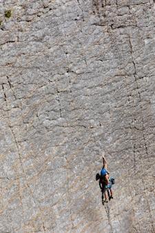 Mulher escalando uma montanha abrupta