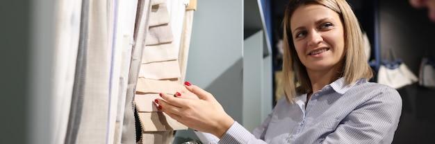 Mulher escolhe a cor do tecido no salão ao lado do consultor com consultoria ao cliente do tablet
