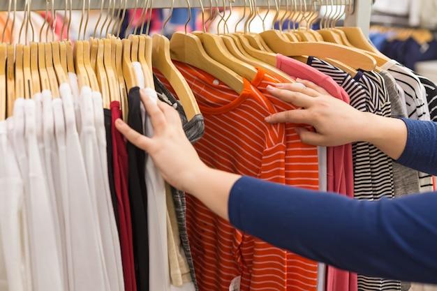 Mulher escolhe camisas em cabides em uma loja de roupas