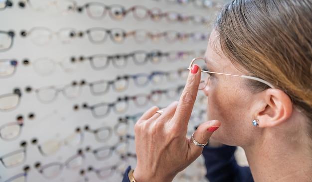 Mulher escolhe e tenta óculos na loja de óptica. copie o espaço