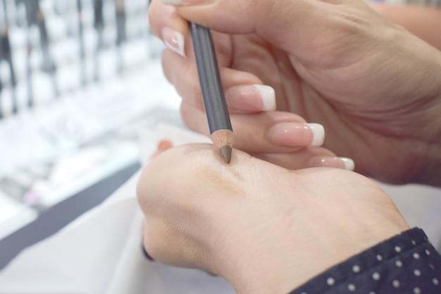 Mulher escolhe lápis de sobrancelha em loja de beleza