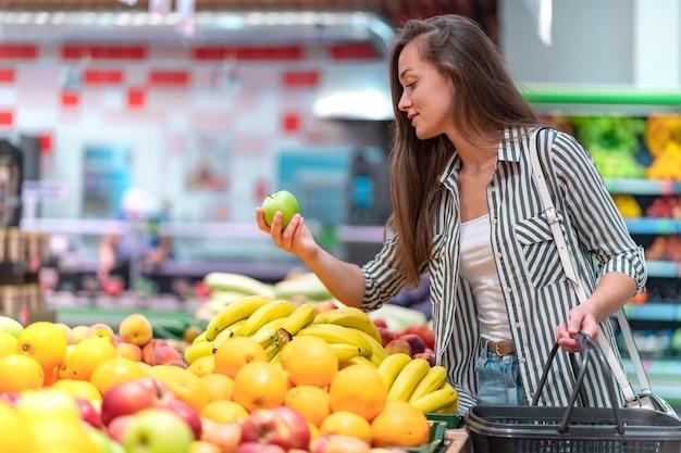 Mulher escolhe maçã verde fresca no departamento de frutas do supermercado. cliente que compra comida na mercearia